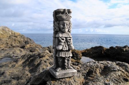 Oude Maya Standbeeld op de rotsen in de buurt van de Oceaan