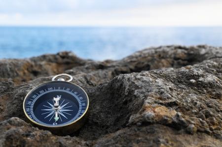 latitude: Orientation Concept - Analogic Compass Abandoned on the Rocks Stock Photo