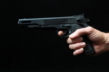 Gun and a Hand on a Black Background photo