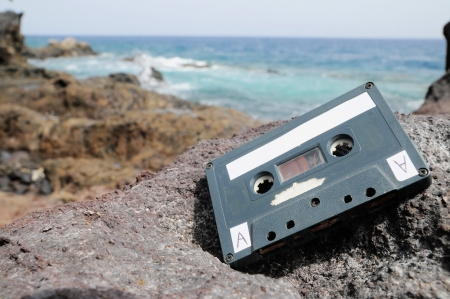 Ancient Musicassette retro en las rocas cerca de la playa photo