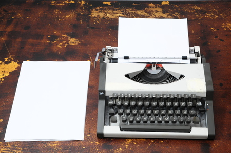 Old Vintage Travel Typewriter on a Brown Wooden Table Stock Photo - 22484829