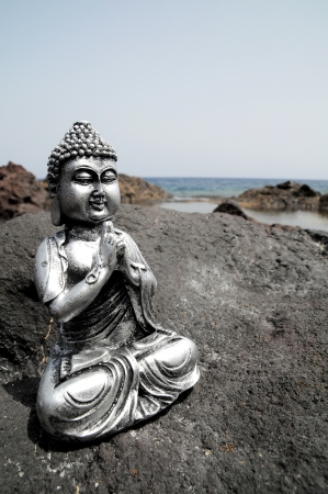 One Ancient Gray Buddha Statue Near The Ocean photo