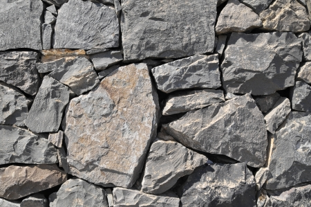 Texture Gray Rock Ancient Wall made of Volcanic Rocks photo