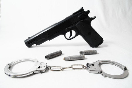 Pistol Gun and Handcuffs on a White  photo