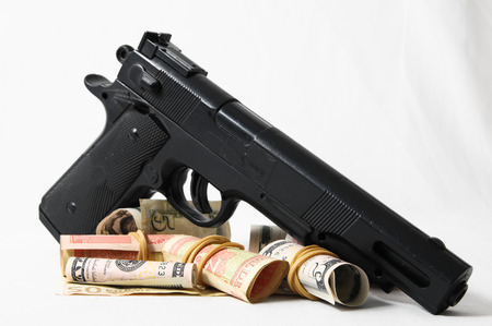 Financial Crime Concept Gun and Money on a White  photo