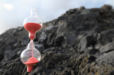 Time Concept - Hourglass Abandoned on the Volcanic Rocks
