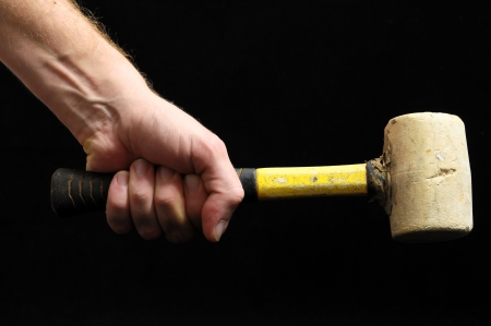 Hammer and a Hand on a Black Background photo