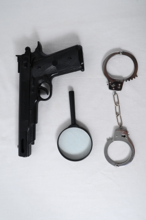 Criminality Concept Gun and Handcuffs on a White Background photo