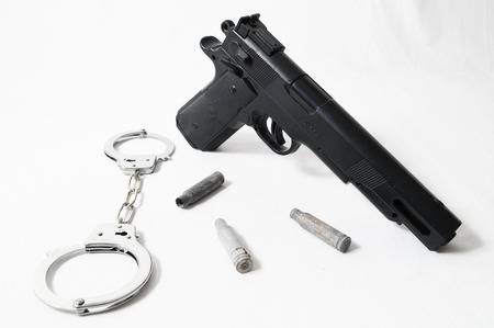 Pistol Gun and Handcuffs on a White Background photo