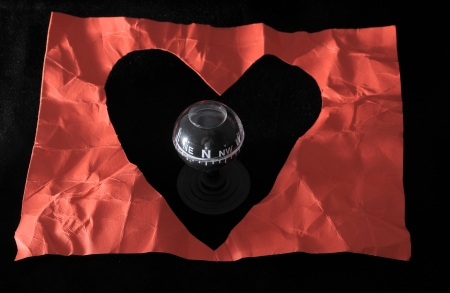 Orientation in Love - Red Paper Heart and Compass on a black Background photo