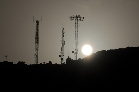 Some Silhouetted Antennas on the top of a Hill photo
