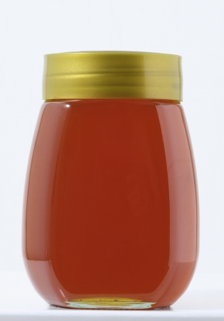 One Full Honey Jar on a White Background photo