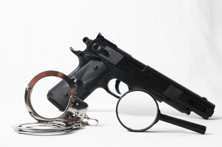 Weapon Crime Concept Gun and Handcuffs on a White Background photo