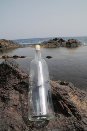 Message in the Bottle on the Rocks near the Beach photo
