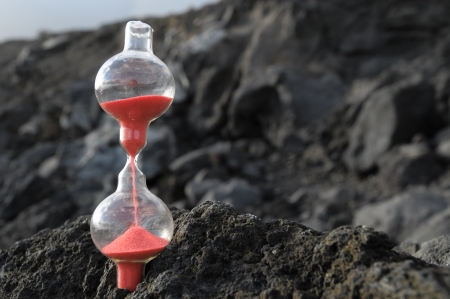Time Concept - Hourglass Abandoned on the Volcanic Rocks photo