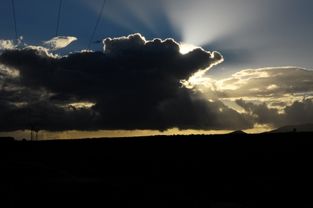 Sun Rays and Clouds over a Blue Sky at Sunset photo