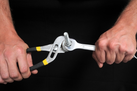 Hand and Strong Pliers over a Black Background Stock Photo - 22942873