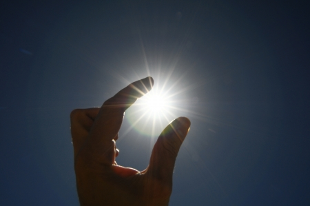 One Hand Catching the Sun Stars on a Blue Background Stock Photo - 22942970
