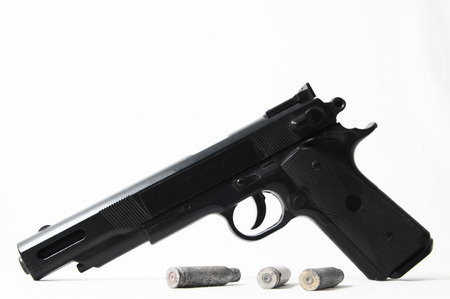 Pistol Gun and Bullets on a White  photo