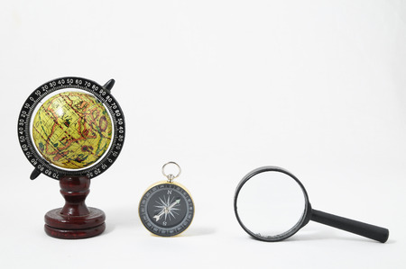 orienting: Vintage Tools Globe Compass and Loupe on a White Background