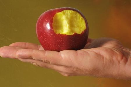 Bitten Red Apple on Hand on a Colred Background Reklamní fotografie