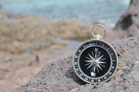 One Compass on the Rocks near the Atlantic Ocean Фото со стока
