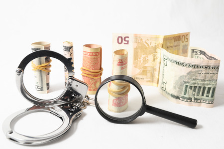 Tax Crime Concept Money and Handcuffs on a White Background photo