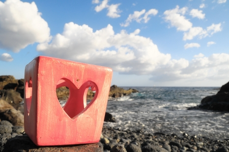 Red Heart Shaped Candle Holder Near the Ocean photo