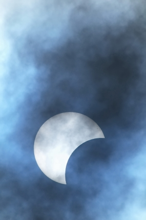 Partial Solar Eclipse on a Cloudy Day 03.11.2013 Stock Photo - 23456259