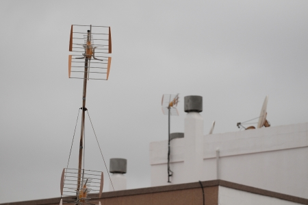 television aerial: Antennas on a Roof over a Cloudy Sky, in Canary Islands, Spain Stock Photo