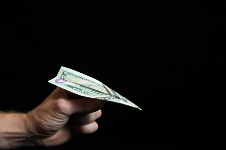 Airplane Dollar And an Hand on a Black Background photo