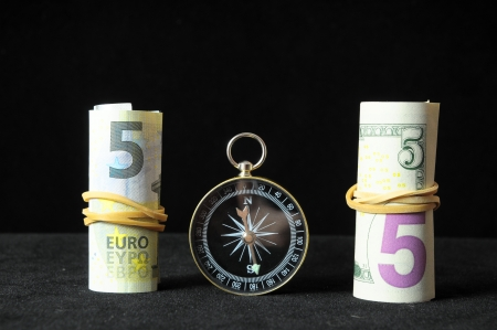 Orientation in  Business Compass and Money on a Black Background photo