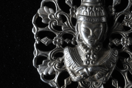 Silver Buddha Pendant Jewel over a Black Background photo