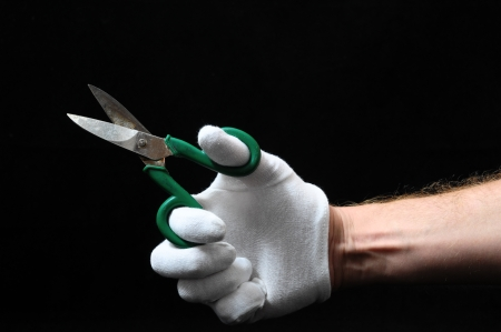 Scissors and Hand on a Black Background photo