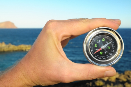 Orientation Concept Male Hand Holding a Metal Compass photo