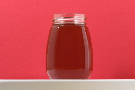 One Full Honey Jar on a Colored Background photo