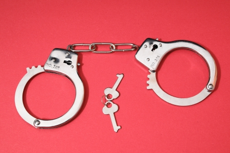 One Pair of Handcuffs on a Colored Background