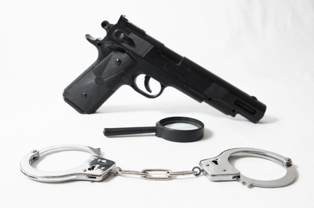 dangerous ideas: Weapon Crime Concept Gun and Handcuffs on a White Background