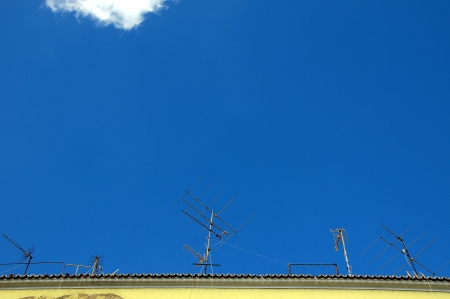 old television antenna on the roof over a blue sky photo