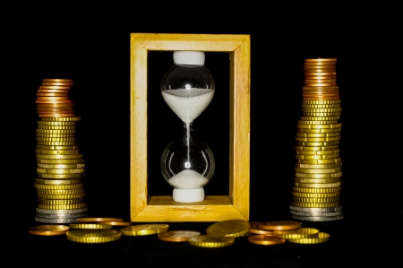 Buisness Time Concept Hourglass and Money on a Black Background photo