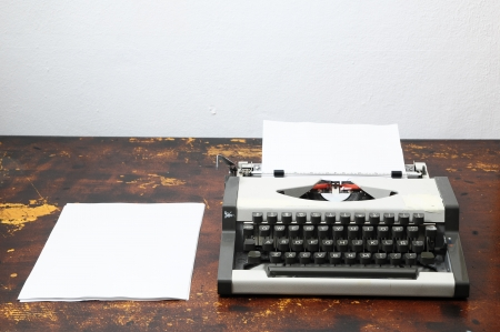 Old Vintage Travel Typewriter on a Brown Wooden Table photo