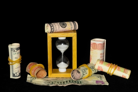 Business Time Concept Hourglass and Money on a Black  photo