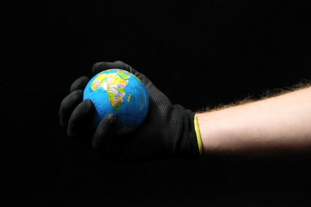 planet Earth and a Hand on Black Background photo
