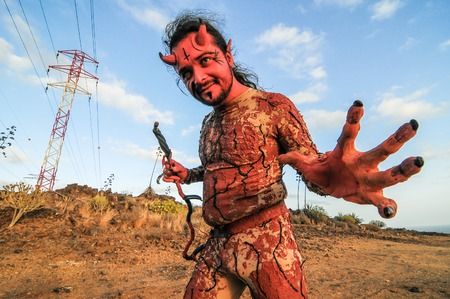 Latin American Man with Long Hairs Masked as a Devil in the Desert photo