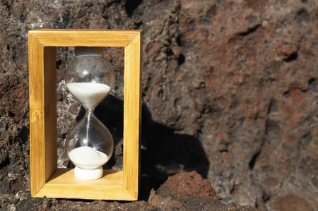 Time Concept White Sand Hourglass on the Volcanic Rocks photo