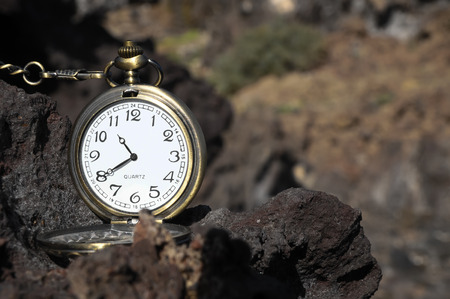 Time Concept Classic Vintage Pocket Clock on the Volcanic Rocks photo