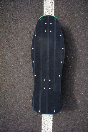 Vintage Style Longboard Black Skateboard on an Empty Asphalt Desert Road photo