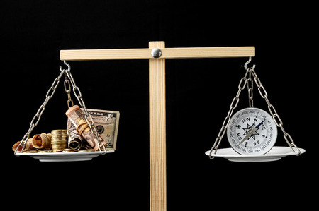 Money and Compass on a Two Pan Balance photo