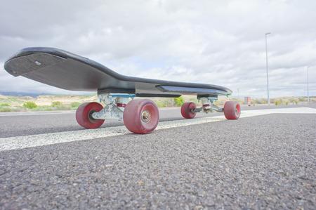 80 s: Hdr Picture Vintage Style Longboard Black Skateboard on an Empty Asphalt Desert Road