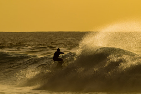 Backlight Silhouette Surfer in the Ocean at Sunset photo